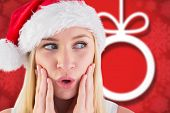 Festive blonde looking surprised with hands on face against blurred christmas background