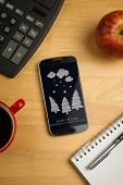 Snow on fir trees against overhead of smartphone with calculator