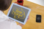 Businesswoman using tablet at desk against happy new year