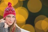 Woman sitting on couch against blurry yellow christmas light circles