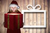 Festive blonde holding a gift against blurred christmas decorations on wood