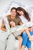 Cute family sitting together on a sofa against house outline in clouds