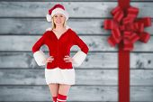Festive blonde smiling at camera against festive bow over wood