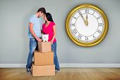 Young couple with moving boxes against room with wooden floor