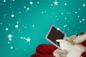 Santa using tablet on the armchair against red background