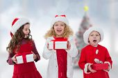 Cute children with gifts against blurry christmas tree in room