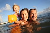 Family swimming in sea at sunset