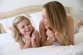 Portrait of cute little girl with mommy laying on bed