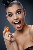 Attractive woman excited, screaming in shock by sparkly gem handheld.