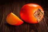 Fresh ripe orange persimmon and slice on a wooden background