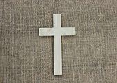 Wooden cross on brown shabby burlap background