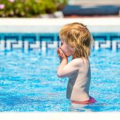 smiling cute little baby girl swims  in the pool in  summer