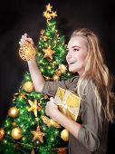 Portrait of cute blond female decorating beautiful Christmas tree over dark background, holding in hands little golden gift box, happy holidays concept