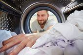 stock photo of laundry  - Man Doing Laundry Reaching Inside Washing Machine - JPG