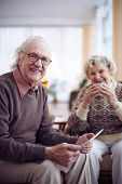 Elderly man with touchpad looking at camera on background of his wife