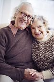 Cheerful senior couple in sweaters looking at camera