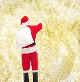 christmas, holidays and people concept - man in costume of santa claus with bag pointing finger from back over yellow lights background