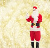 christmas, holidays, gesture and people concept - man in costume of santa claus pointing fingers over yellow lights background