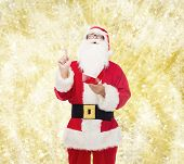 christmas, holidays, gesture and people concept - man in costume of santa claus with notepad pointing finger up over yellow lights background