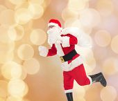 christmas, holidays and people concept - man in costume of santa claus running with bag over beige lights background