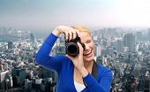 photography, technology and people concept - smiling young woman taking picture with digital camera over city background