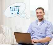 people, leisure and technology concept - smiling young man with laptop computer and trolley icon shopping online at home