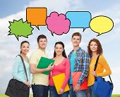 school, education, communication and people concept - group of smiling teenagers with folders and school bags over blue sky and grass background with doodles
