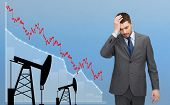 business, people, crisis, finances and economics concept - businessman with forex chart and pumpjacks touching his head over blue background