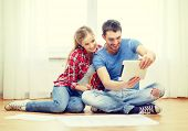repair, building, renovation and home concept - smiling couple looking at tablet pc at home