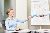 business and people concept - smiling businesswoman receiving papers from someone in office