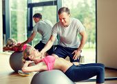 fitness, sport, exercising and diet concept - smiling young woman and personal trainer in gym