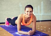 fitness, sport, training, future technology and lifestyle concept - smiling woman doing exercises on mat in gym over cardiogram projection