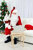 Modern Santa Claus sitting on sofa and using computer