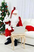 Modern Santa Claus sitting on sofa and using computer