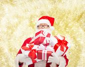 christmas, holidays and people concept - man in costume of santa claus with gift boxes over yellow lights background
