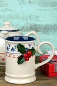 Christmas composition with cup and teapot of hot drink, on wooden table