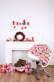 Chair near the Christmas fireplace with firewood and present boxes on wooden floor and white wall background