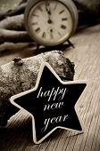 the sentence happy new year written in a star-shaped chalkboard, on a rustic wooden surface, in sepia tone