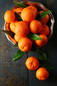 Fresh ripe mandarins on plate, on wooden background