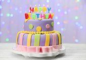 Delicious birthday cake on shiny light background