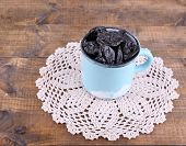 Cup filled with prunes on lace doily, on wooden background