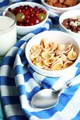 Various sweet cereals and berries in ceramic bowls and glass with milk on color towel background