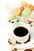 Gentle colorful macaroons in glass bowl and black coffee in mug isolated on white