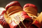 Retro pair of red and yellow boxing gloves lying on a table.