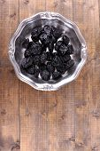 Metal plate of prunes on wooden background