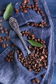 Green petal near the spoon of coffee beans on blue wooden background with jeans material