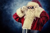 Modern Santa Claus in sunglasses over dark background. Christmas.