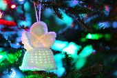 Knitted Christmas angel on Christmas lights background