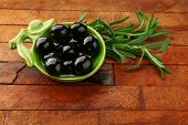 Black marinated olives in small green saucepan with oil near branch on rustic background