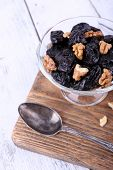 Wooden board with glass bowl of prunes and walnuts, shell and spoon on color wooden background
